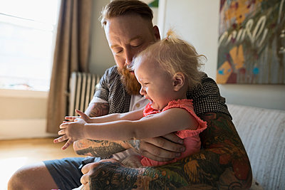 Father with tattoos holding crying daughter - p1192m1158176 by Hero Images