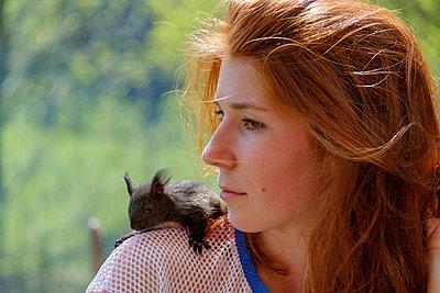 Portrait of redheaded teenage girl with squirrel on her shoulder - p300m1587886 von Lisa und Wilfried Bahnmüller