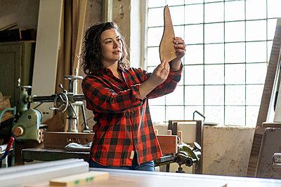 Carpenter holding workpiece in her workshop - p300m2170600 by Robijn Page