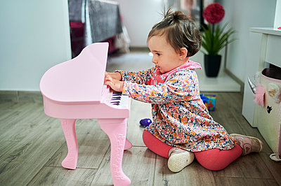 Baby playing piano while sitting on floor at home - p300m2275597 by Kiko Jimenez