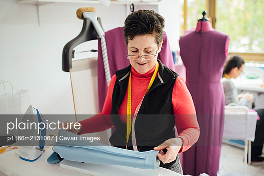 senior and cheerful woman ironing in a fashion design studio - p1166m2131067 by Cavan Images