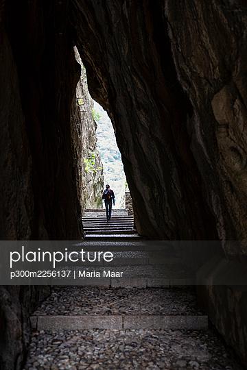 Male tourist exploring amidst soapstone cave at quarry in Parco Archeologico Botanico del Paradiso, Valchiavenna, Chiavenna, Province of Sondrio, Lombardy, Italy - p300m2256137 by Maria Maar
