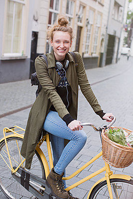 Portrait smiling young woman with headphones riding bicycle with produce in basket - p1023m1443247 by Sam Edwards