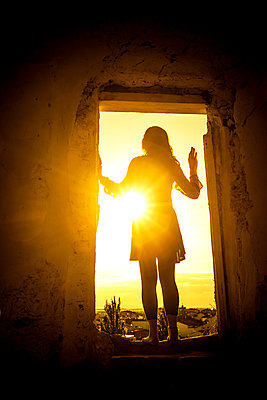 Silhouette einer Frau in einer Tür bei Sonnenuntergang - p248m2107550 von BY