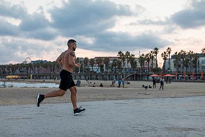 Barechested muscular man running on waterfront promenade - p300m2080916 von Mauro Grigollo