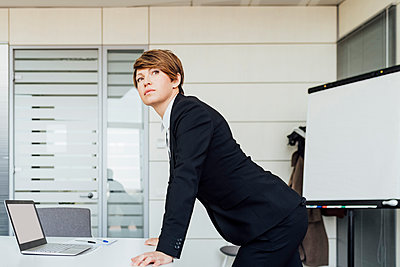 Contemplating businesswoman looking away while leaning on desk in office - p300m2276098 by Eugenio Marongiu