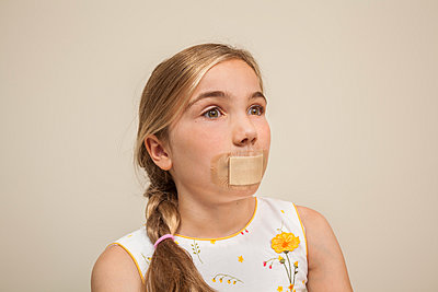 Preteen girl with a bandage over her mouth - p397m887512 by Peter Glass