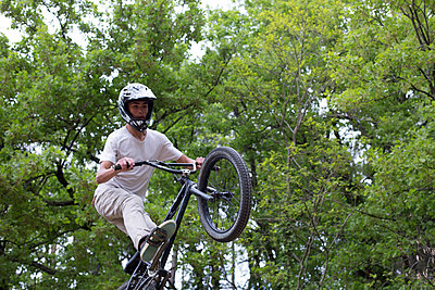 Biker jumping in the forest - p445m912700 by Marie Docher