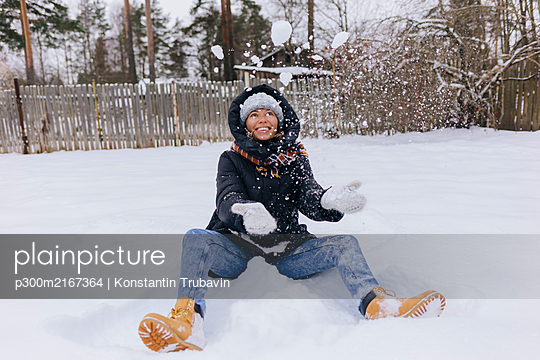 Happy woman sitting on snow field playing with snowballs - p300m2167364 by Konstantin Trubavin