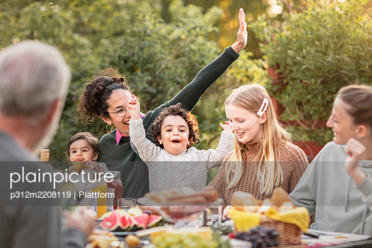 Family having meal in garden - p312m2208119 by Plattform