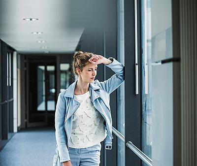 Businesswoman leaning against window in office passageway - p300m2023606 von Uwe Umstätter