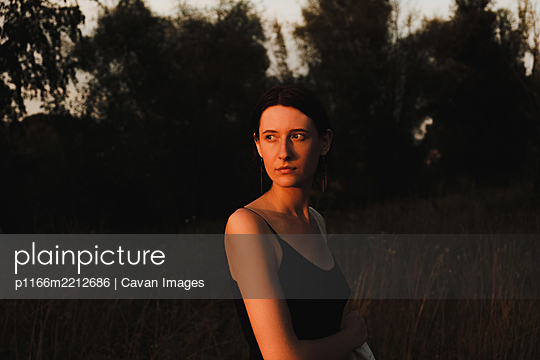 Young adult woman in dress posing at sunset. Low key portrait of - p1166m2212686 by Cavan Images
