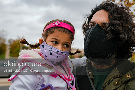 father and daughter with protective face masks and halloween costume - p1166m2224137 by Cavan Images