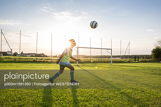 Young football player heading the ball on football ground at sunset - p300m1581350 von Fotoagentur WESTEND61