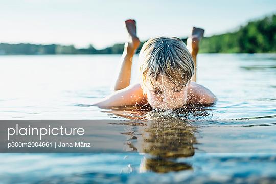 Boy in a lake blowing into water - p300m2004661 von Jana Mänz