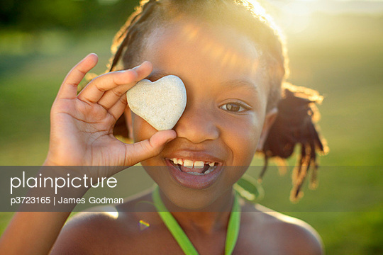 Young girl holding heart shaped rock - p3723165 by James Godman