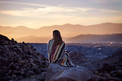 Rear view of woman wrapped in blanket sitting on rock against sky - p1166m1406820 by Cavan Images