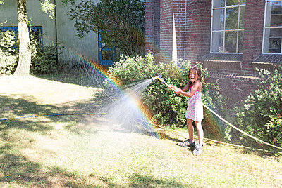 Girl watering the garden - p1231m2013516 by Iris Loonen