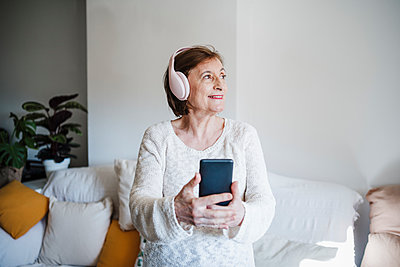 Smiling woman holding mobile phone while listening music through headphones against sofa - p300m2265596 by Eva Blanco