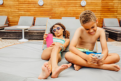 Mixed race children taking selfie with cell phones on patio - p555m1408568 by Inti St Clair