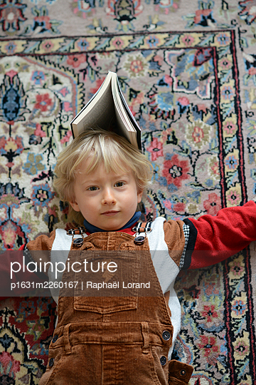 Toddler playing with a book - p1631m2260167 by Raphaël Lorand