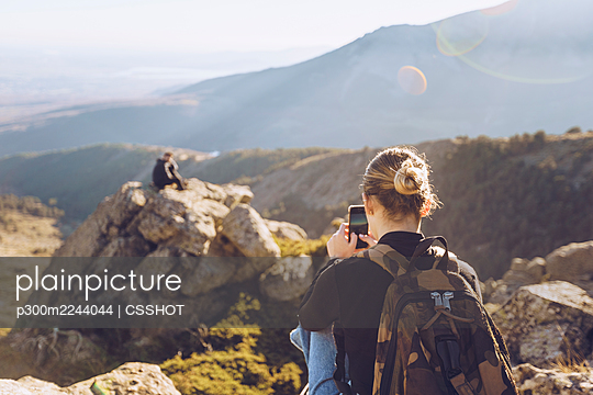 Young woman photographing male friend sitting on top of mountain - p300m2244044 by CSSHOT