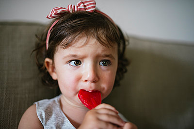 Cute baby girl eating a heart shaped lollipop at home - p300m2012541 von Gemma Ferrando