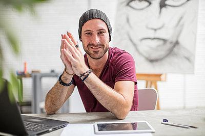 Portrait of confident artist sitting at his desk in studio - p300m2013305 von zerocreatives