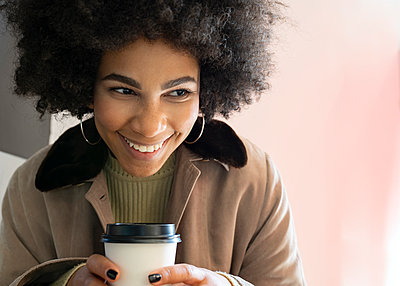 Smiling woman with disposable coffee cup looking away while sitting at cafe - p300m2253232 by Jose Carlos Ichiro