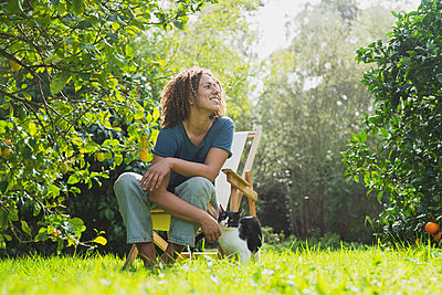 Smiling curly haired woman looking away while sitting on chair by cat in garden - p300m2267372 by Steve Brookland