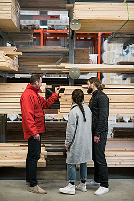 Salesman assisting couple in buying wooden planks in hardware store - p426m1407298 by Maskot