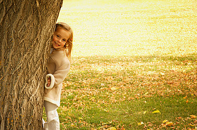 A girl peeks from behind a tree - p4421770f by Design Pics
