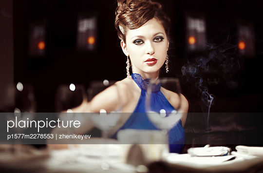 Beautiful stylish lady with perfect hairstyle and makeup sitting in the splendid restaurant - p1577m2278553 by zhenikeyev