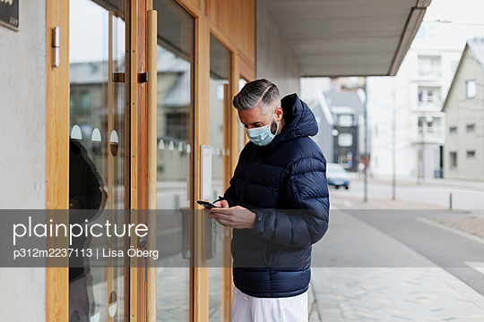 Man wearing face mask using phone in front of entrance door - p312m2237113 by Lisa Öberg