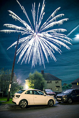 Fireworks over cars and residential buildings - p1072m2173592 by Neville Mountford-Hoare