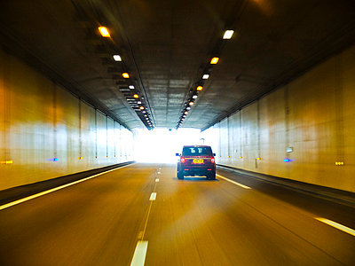 Rear view of Range Rover driving through tunnel  - p1072m829233 by Neville Mountford-Hoare