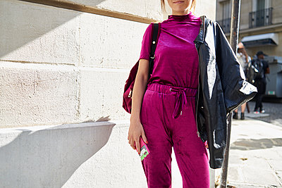 Woman in magenta top and track pants in street, crop - p1407m1508540 by Guerrilla