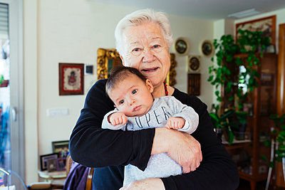 Portrait of smiling great-grandmother holding baby - p300m1356157 by Gemma Ferrando