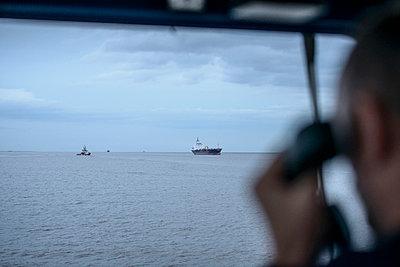 Worker on tugboat talking on phone - p429m747093f by Monty Rakusen