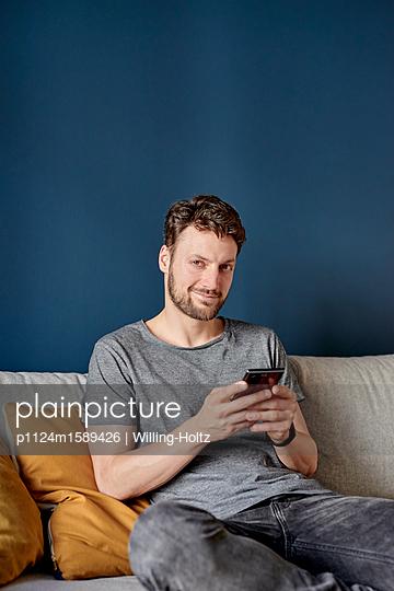 Junger Mann schreibt SMS auf Smartphone - p1124m1589426 von Willing-Holtz