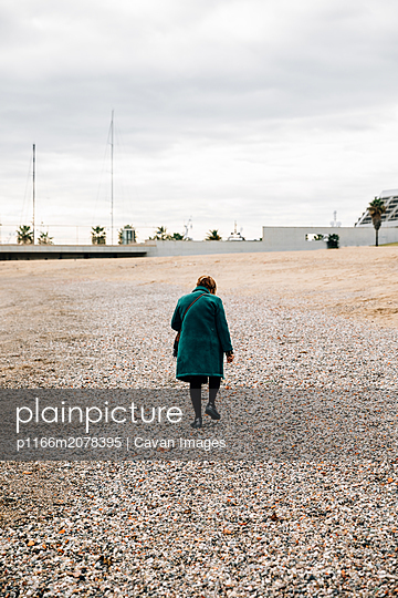 View from behind of an elderly woman walking - p1166m2078395 by Cavan Images