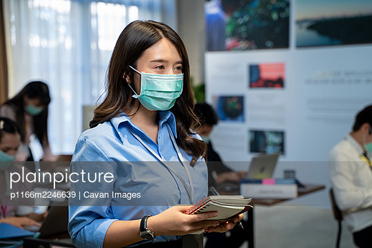 Asian business people wearing protective mask to Protect Against - p1166m2246639 by Cavan Images