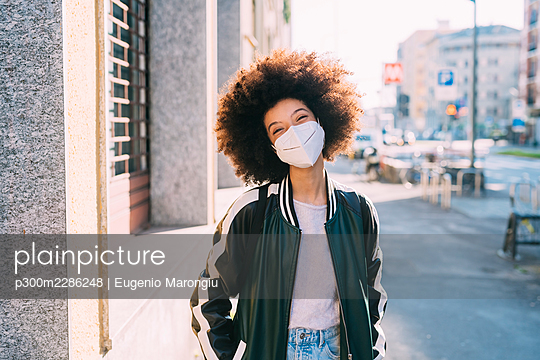 Curly hair woman with protective face mask standing on footpath - p300m2286248 by Eugenio Marongiu
