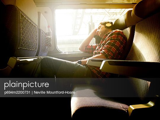 Young Man asleep on Train - p694m2200731 by Neville Mountford-Hoare