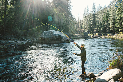 Side view of man Fly-fishing while standing on rock in river at Yosemite National Park - p1166m2040354 by Cavan Images