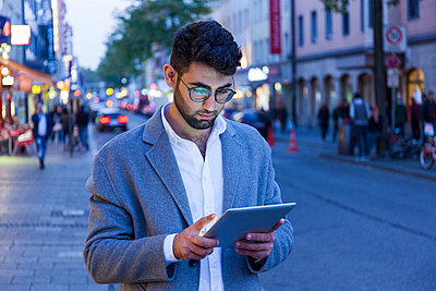 Germany, Munich, young businessman using digital tablet in the city at dusk - p300m2070084 by Tom Chance