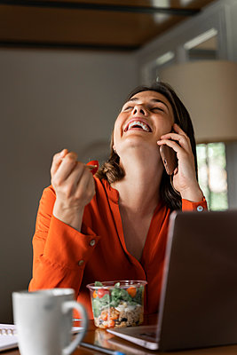 Happy businesswoman talking on mobile phone while eating salad at home - p300m2206518 by VITTA GALLERY
