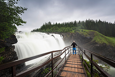Man at lookout of waterfall in Jamtland, Sweden - p352m1536558 by Calle Artmark