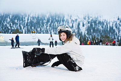 Girl sitting by ski slope - p4267906f by Serny Pernebjer