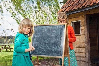 Two girls outdoors with blackboard - p924m665030f by Mieke Dalle
